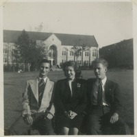 Three Students Sitting On Bench In Front of Johnston Building