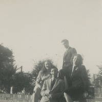 Four Students Sitting On a Wall On Campus