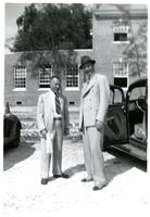 Two men standing next to a black car