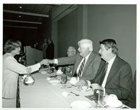Tip O'Neill shaking the hand of a woman at a luncheon with Claude Pepper