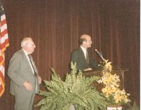 Claude Pepper and an unidentified man standing at a podium