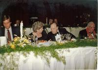 Bob Hope talking to a guest sitting at a banquet table at Claude Pepper's 84th birthday party