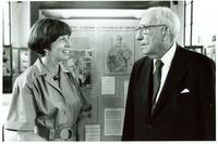 Claude Pepper talking to a woman in front of a display at the Mildred and Claude Pepper Library