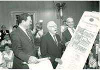 Claude Pepper holding a large scroll at the National Institute on Aging's Centenarians' Day