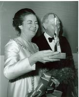 Unidentified woman holding a glass award at a formal event