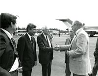 Claude Pepper and Bob Graham standing with a small group on an airport tarmac