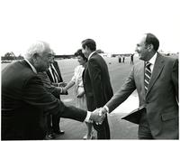 Two men shaking hands on an airport tarmac