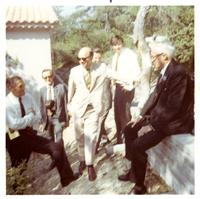 United States  Ambassador to France Arthur K. Watson sitting on a stone wall with a small group
