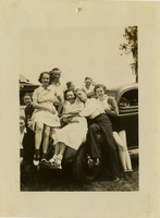 Elizabeth (Bette) Evans Pictured With Friends Around a Black Vehicle
