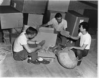Three men with pottery artifacts