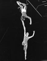 Two circus performers on a trapeze