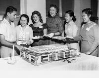 Group of students standing around a cake