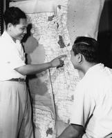 Two students standing in front of a map