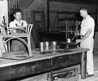 Two men repairing a table and chair each