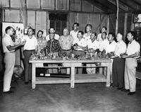 Group of men standing around a table in an outdoor warehouse