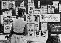 Unidentified student standing in front of election fliers