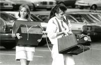 Two students carrying electronics