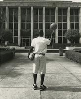 Student holding books and a basketball in front of Strozier Library