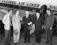 Men stand with Charles Sawyer next to plane