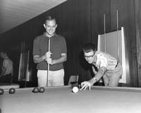 Two unidentified male students playing pool