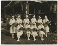 Nursing students holding bouquets of flowers