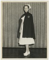 Nursing student wearing Red Cross uniform and cape