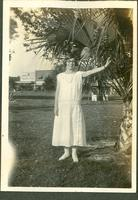 Young woman standing next to a palm