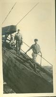 Two men walking down a wooden structure