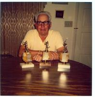 Ben Fuller sitting with trophies on table