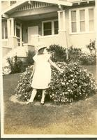 Young girl posing in front of flowering bush