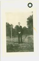 Young man standing in front of a fence