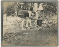 Barefoot child stirring a pot over fire with a stick