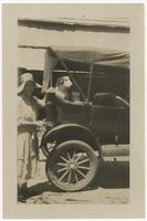 A woman and a dog posing with a car