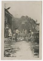 Litter Bearers in Front of Destroyed Motor Torpedo Squadron 3 Warehouse