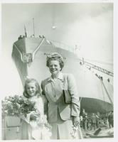 Unidentified woman and girl standing in front of a ship