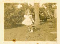 Young girl running in front yard