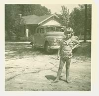 Young girl posing in front of a car