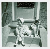 Young girl in Easter dress and dog sitting on steps