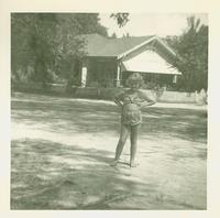 Young girl posing in front of a house