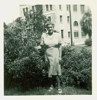 Woman posing by a bush