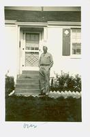 Uniformed man standing in front of a house