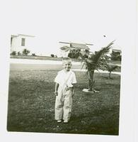 Young boy standing on a lawn