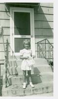 Young child standing on front steps