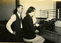 Elizabeth Anne Webb Typing with Boss Standing Behind Her