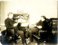 Two men sitting in an office reading