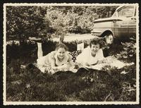 Betty Dirac, and possibly her niece, laying on a blanket on the ground outdoors