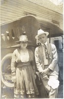 Woman and Man in Hats in Front of an Automobile