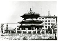 A three-tiered pagoda and tall modern building in background