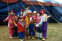 Eleven clowns standing in front of a circus tent