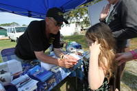 FSU Ocean Atmospheric Fair Representative providing handout to young girl